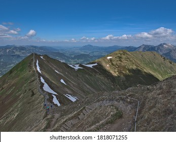 Panoramic view of alpine hiking trail with few hikers leading over a ridge below Fellhorn peak (2,037 m) near Oberstdorf, Allgäu, Alps, Bavaria, Germany with wide view in northern direction.