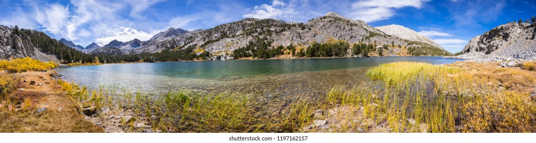 Panoramic view of alpine lake surrounded by the rocky ridges of the Eastern Sierra mountains; Long Lake, Little Lakes Valley trail, John Muir wilderness, California