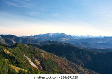 Panoramic view of a alpine mountain landscape with colorful trees (Red, yellow and green) on a sunny day in late summer (autumn). Snow covered summits in the background. Hiking in the chiemgau alps.