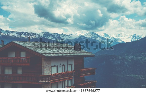 Panoramic view of the alpine village. Beautiful old wooden house and snow covered Alps mountains on the background. Switzerland, Europe.
