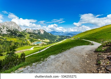 Panoramic view of Alps mountains in summer. Great view of beautiful landscape. Blue sky with clouds, green meadows, tourists on hiking trails. Nassfeld, Hermagor. Carinthia. Austria.