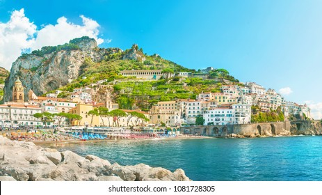 panoramic view of Amalfi beach and houses from stone pier on sunny summer day, Salerno, Campania, Italy
