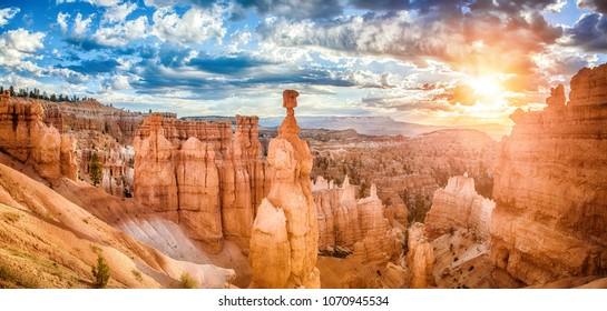 Panoramasicht auf die fantastischen hoodoos Sandsteinformationen im malerischen Bryce Canyon Nationalpark in schönem goldenen Morgenlicht bei Sonnenaufgang mit dramatischem Himmel und blauem Himmel, Utah, USA
