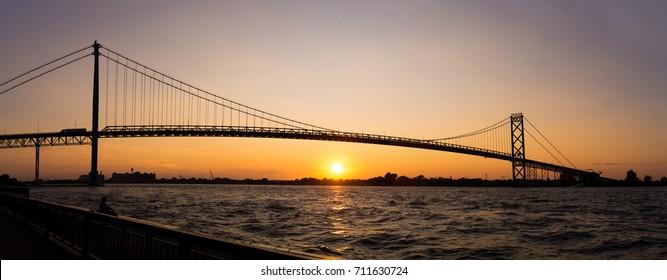 Panoramic view of Ambassador Bridge connecting Windsor, Ontario to Detroit Michigan at sunset time