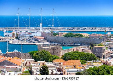 Panoramic view of the ancient medieval walls of the Rhodes Town and the old city buidings near the Hippocrates Square. In the background, luxury cruise ships and yachts dock in the new Mandraki port