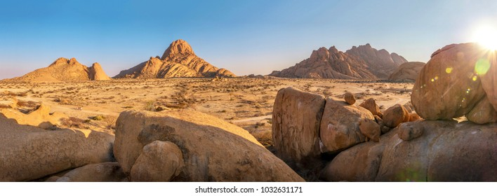 Panoramic view of the ancient Spitzkoppe region of Damaraland, Namibia, with its massive boulders, rocky hills and mountains in early morning light.