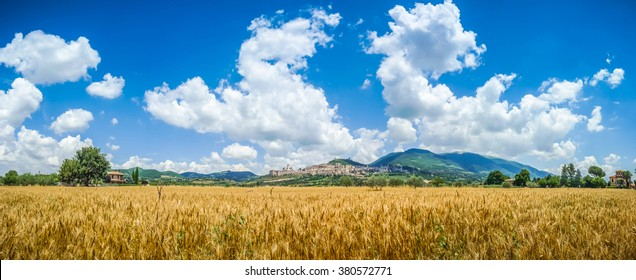 Panoramic view of the ancient town of Assisi with dramatic cloudscape and golden harvest fields, Umbria, Italy