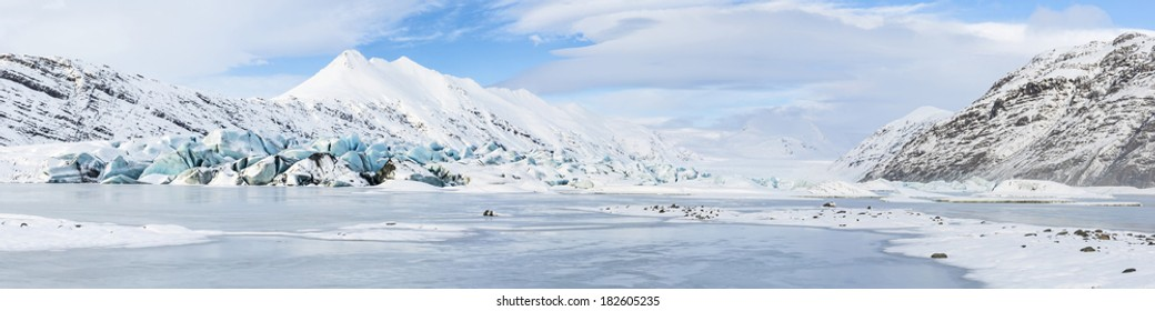 Panoramic view of the aqua blue tongue of Heinabergs glacier and frozen glacial lagoon in Southeast Iceland near Hofn