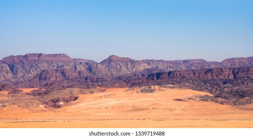 Panoramic view of the Arava valley: the border between Israel to the west and Jordan to the east and  Wadi Rum drainage area with the colorful red sands, cliffs and sharp-topped granite mountains.
