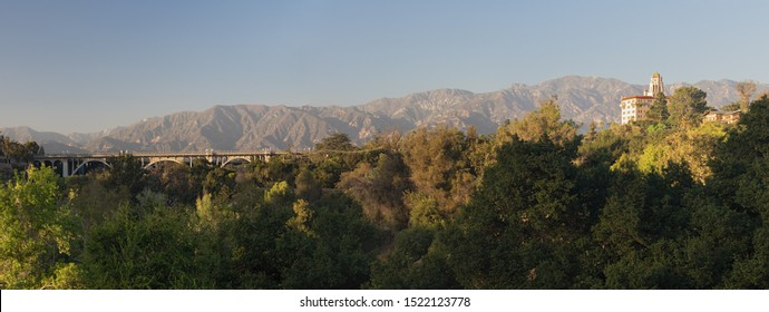 Panoramic view of the Arroyo Seco, the Colorado Street Bridge, and the Richard H. Chambers Courthouse against the San Gabriel Mountains in Pasadena.