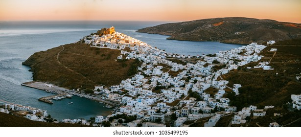 Panoramic view of Astypalaia Chora with the sun setting and a small spot of light remaining on top of the fortress