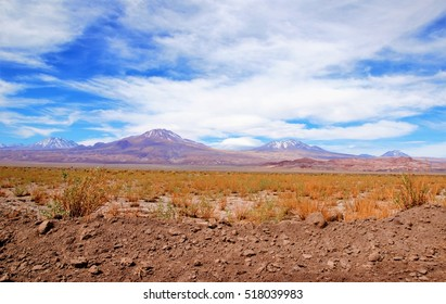 Panoramic view of the Atacama desert with a mountain range in the background and a blue sky with clouds close to San Pedro de Atacama in Chile, South America