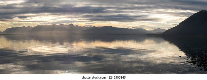 Panoramic view of the Atlantic Ocean and the reflection of the light in the water during sunset in the East Fjords, Iceland