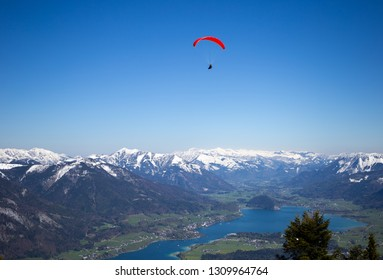 Panoramic view of austrian alps and  paraglider flying over the mountains and lake Wolfgangsee. Austria. April.
