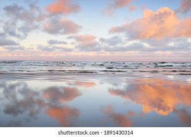Panoramic view of the Baltic sea from a sandy shore. Clear sunset sky, colorful glowing pink clouds, soft light. Symmetry reflections on water, natural mirror. Weather, winter, climate change, nature