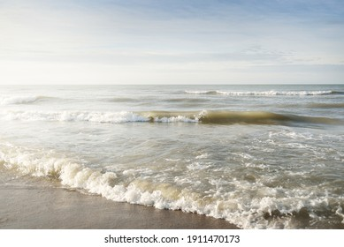 Panoramic view of the Baltic sea from a sandy shore (sand dunes). Clear sky with glowing clouds, waves and water splashes. Idyllic seascape. Warm winter weather, climate change, nature. Denmark