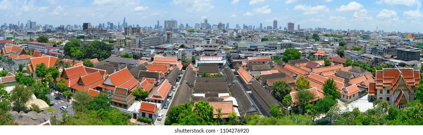 Panoramic view of Bangkok from the Wat Saket, with traditional buildings in the foreground and modern buildings in the background.