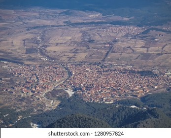 Panoramic view of the Bansko town. Old european medieval town with narrow streets and red roofs surrounded by green forest, fields and mountains. Bansko ski resort, Bulgaria.