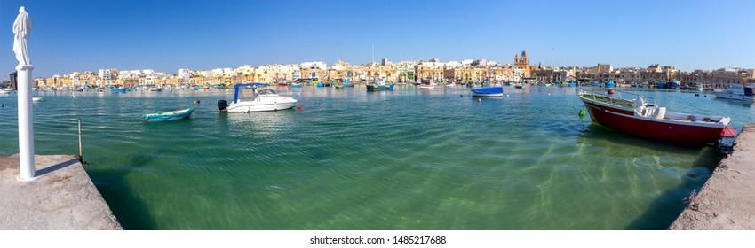 Panoramic view of the bay fishing boats and the village of Marsaxlokk. Malta.