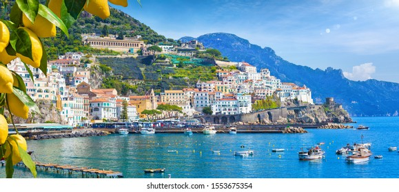 Panoramic view of beautiful Amalfi on hills leading down to coast, Campania, Italy. Amalfi coast is most popular travel and holiday destination in Europe. Ripe yellow lemons in foreground.