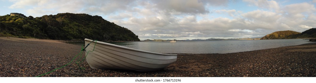 Panoramic view of beautiful bay with sailing boat in the water and tender dinghy boat on the beach in New Zealand