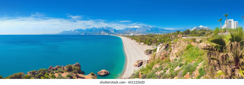Panoramic view of beautiful blue lagoon and Konyaalti beach in popular resort city Antalya, Turkey. Sunny day, high mountains on horizon.