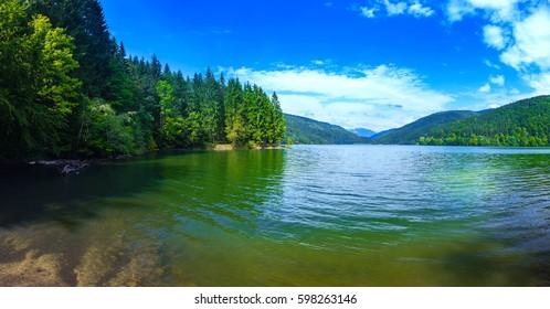Panoramic view of beautiful lake and spruce forest in mountains at sunshine