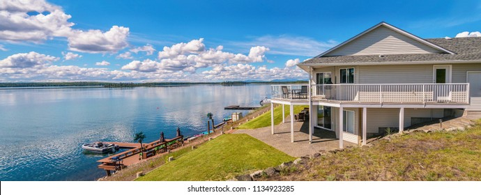 Panoramic view of a beautiful, large modern luxury summer holiday home, featuring sun decks, glass railings, and large windows, set beside a small lake in central British Columbia, Canada.