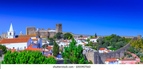 Panoramic view of the beautiful medieval historic center village of Obidos and Castle of Obidos. Wonderful romantic afternoon landscape at sunny weather. District of Leiria, in the centre of Portugal.