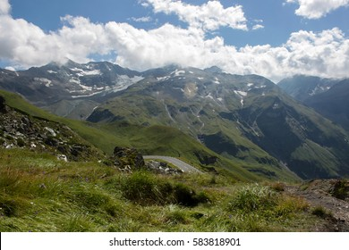 Panoramic view of beautiful mountain landscape in the Alps with green mountain pastures with pines and snow capped mountains in the background in summer. Unesco area with famous Grossglockner road.