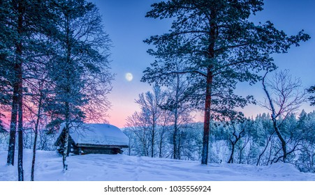 Panoramic view of beautiful Nordic winter wonderland scenery with traditional wooden shelter in  scenic evening light at sunset with moonlight in Scandinavia, Northern Europe