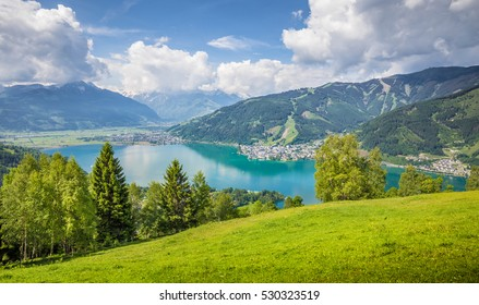 Panoramic view of beautiful scenery in the Alps with clear lake and green meadows full of blooming flowers on a sunny day with blue sky and clouds in springtime, Zell am See, Salzburger Land, Austria