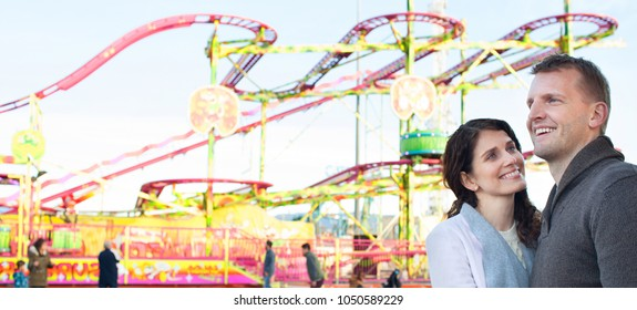 Panoramic view of beautiful tourist couple visiting colorful amusement park with roller coaster ride, hugging outdoors. Man and woman enjoying funfair carnival together, leisure recreation lifestyle.
