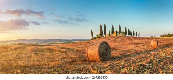 Panoramic view of beautiful Tuscany landscape with traditional farm house and hay bales in golden evening light at sunset, Val d'Orcia, Italy
