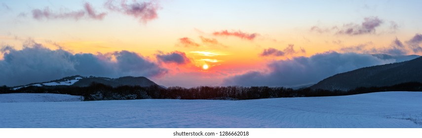 Panoramic view to beautiful vibrant winter sunset in the mountains