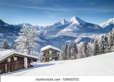 Panoramic view of beautiful white winter wonderland mountain scenery in the Alps with traditional old wooden mountain chalets on a cold sunny day with blue sky and clouds