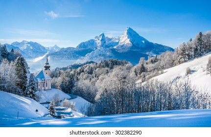 Panoramic view of beautiful winter landscape in the Bavarian Alps with pilgrimage church of Maria Gern and famous Watzmann massif in the background, Nationalpark Berchtesgadener Land, Bavaria, Germany