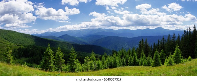 Panoramic view of beautiful wooded hills mountains and blue sky with white clouds.