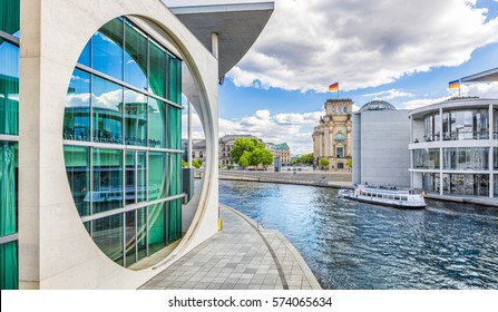 Panoramic view of Berlin government district with excursion boat on Spree river passing famous Reichstag building and Paul Lobe Haus on a sunny day with blue sky and clouds, Berlin Mitte, Germany