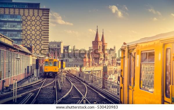 Panoramablick auf die Berliner U-Bahn mit Oberbaum Bridge im Hintergrund bei goldenem Abendlicht bei Sonnenuntergang mit Retro-Hip-Filter im Instagram-Stil, Berlin Friedrichshain-Kreuzberg