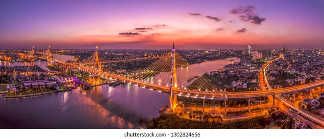 Panoramic view of Bhumibol bridge crossing the Chaophraya river with Bangkok cityscape under twilight sky. Thai words and logo at bridge is the name of them, not any commercial meaning.