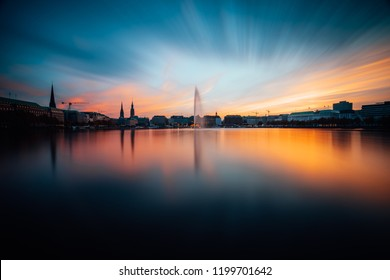 Panoramic view of Binnenalster, Inner Alster Lake in golden and blue evening light at sunset, Hamburg, Germany. Blue hour. Long exposure