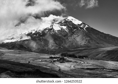 Panoramic view in black and white of El Chimborazo snowy volcano and surrounding crops in the Andes mountain range in Ecuador