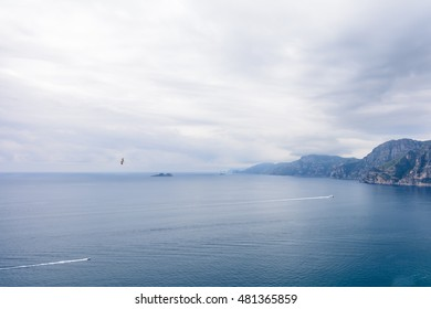 Panoramic view of blue clear sea. Horizontal view with coastal fragments, clear sea, white sky and some boats.