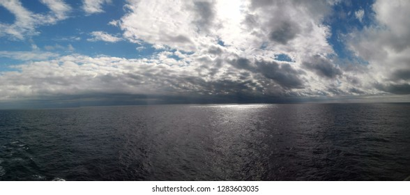 Panoramic view of blue sky with cumulus clouds separated from the sun, floating above the ocean - perfect for background. Blue pastel heaven in soft focus. Simple shot of peaceful and beautiful nature