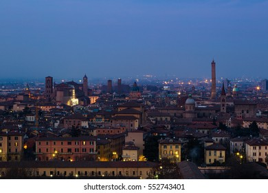 Panoramic view of Bologna, Italy at night. Colorful sky over the historical city center with old buildings, the towers Asinelli and Garisenda, and Church