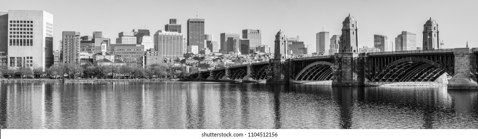 Panoramic view of Boston, Massachusetts from the Cambridge side of the Charles River. In black and white with the Longfellow Bridge prominent in the foreground.