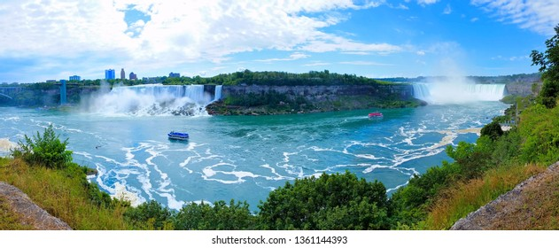 Panoramic view of the both Canadian and American sides of Niagara Falls under blue skies