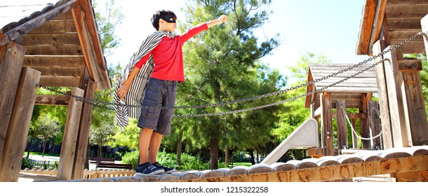 Panoramic view of boy child standing on wooden structure bridge, park playground dressed as superhero pretending to fly, sunny outdoors. Kid role playing imagination, leisure recreation fun lifestyle.