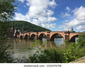 Panoramic view of a bridge on a river in Haidelberg, Deutschland during partly cloudy summer day